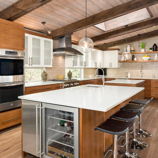 Large mid-century modern kitchen ideas - Kitchen - large 1950s l-shaped brown floor and light wood floor kitchen idea in Portland with solid surface countertops, beige backsplash, stainless steel appliances, two islands, flat-panel cabinets, an undermount sink and light wood cabinets