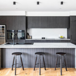 Photo of a large contemporary galley kitchen in Melbourne with a double-bowl sink, flat-panel cabinets, dark wood cabinets, white splashback, subway tile splashback, panelled appliances, light hardwood floors, with island, beige floor and grey benchtop.