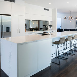 Photo of a contemporary kitchen in Melbourne with flat-panel cabinets, white cabinets, mirror splashback, stainless steel appliances, dark hardwood floors, with island, brown floor and white benchtop.