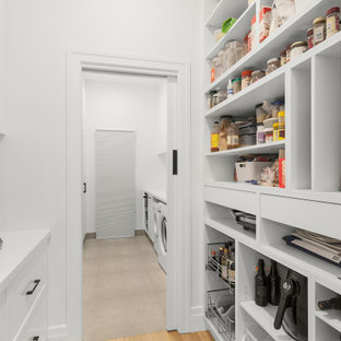 Inspiration for a mid-sized contemporary single-wall kitchen pantry in Melbourne with shaker cabinets, white cabinets, quartz benchtops, white splashback, black appliances, light hardwood floors, beige floor and white benchtop.