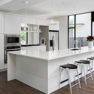 Contemporary kitchen inspiration - Example of a trendy u-shaped medium tone wood floor and brown floor kitchen design in Atlanta with an undermount sink, flat-panel cabinets, white cabinets, stainless steel appliances, an island and white countertops