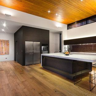 メルボルンの広いコンテンポラリースタイルのおしゃれなキッチン (フラットパネル扉のキャビネット、白いキャビネット、大理石カウンター、シルバーの調理設備、無垢フローリング、茶色いキッチンパネル、レンガのキッチンパネル) の写真