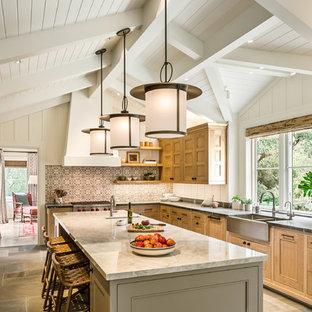 Geschlossene Maritime Küche mit Landhausspüle, Schrankfronten mit vertiefter Füllung, hellen Holzschränken, bunter Rückwand, Elektrogeräten mit Frontblende, Kücheninsel und grauem Boden in Santa Barbara