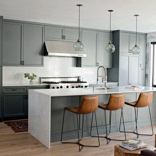 サンフランシスコのトランジショナルスタイルのおしゃれなキッチン (アンダーカウンターシンク、シェーカースタイル扉のキャビネット、緑のキャビネット、シルバーの調理設備、淡色無垢フローリング、白いキッチンカウンター) の写真