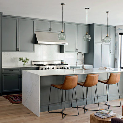 Transitional galley light wood floor open concept kitchen photo in San Francisco with an undermount sink, shaker cabinets, green cabinets, stainless steel appliances, an island and white countertops