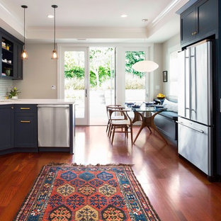 Photo of a large traditional u-shaped kitchen/diner in San Francisco with shaker cabinets, blue cabinets, white splashback, ceramic splashback, stainless steel appliances, a breakfast bar, a double-bowl sink, engineered stone countertops and medium hardwood flooring.