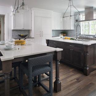 Große Klassische Wohnküche in L-Form mit Doppelwaschbecken, Schrankfronten mit vertiefter Füllung, Mineralwerkstoff-Arbeitsplatte, Küchenrückwand in Grau, Rückwand aus Glasfliesen, Küchengeräten aus Edelstahl, braunem Holzboden, zwei Kücheninseln, braunem Boden und weißer Arbeitsplatte in Chicago