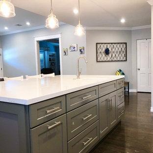 ロサンゼルスの中くらいのトラディショナルスタイルのおしゃれなキッチン (ドロップインシンク、落し込みパネル扉のキャビネット、グレーのキャビネット、クオーツストーンカウンター、白いキッチンパネル、セラミックタイルのキッチンパネル、シルバーの調理設備、濃色無垢フローリング、茶色い床、白いキッチンカウンター) の写真