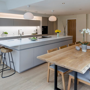 Inspiration for a medium sized contemporary single-wall kitchen in West Midlands with flat-panel cabinets, white cabinets, white splashback, integrated appliances, an island, beige floors and white worktops.