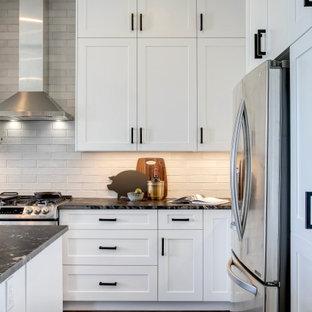 Mittelgroße Landhaus Küche in L-Form mit Unterbauwaschbecken, Schrankfronten im Shaker-Stil, weißen Schränken, Granit-Arbeitsplatte, Küchenrückwand in Weiß, Rückwand aus Backstein, Küchengeräten aus Edelstahl, Vinylboden, Kücheninsel, braunem Boden und schwarzer Arbeitsplatte in Calgary