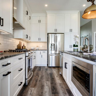 Photo of a mid-sized country l-shaped kitchen in Calgary with an undermount sink, shaker cabinets, white cabinets, granite benchtops, white splashback, brick splashback, stainless steel appliances, vinyl floors, with island, brown floor and black benchtop.