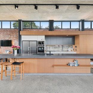 Offene, Zweizeilige Industrial Küche mit Einbauwaschbecken, flächenbündigen Schrankfronten, hellen Holzschränken, Rückwand-Fenster, Betonboden, Kücheninsel, grauem Boden und grauer Arbeitsplatte in Sonstige