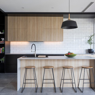 Design ideas for a mid-sized contemporary l-shaped kitchen in Adelaide with a double-bowl sink, flat-panel cabinets, light wood cabinets, quartz benchtops, white splashback, subway tile splashback, stainless steel appliances, with island and grey floor.