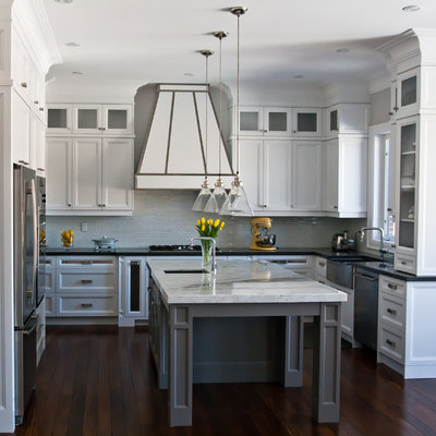 Large transitional u-shaped medium tone wood floor kitchen photo in Toronto with a farmhouse sink, recessed-panel cabinets, white cabinets, gray backsplash, glass tile backsplash, stainless steel appliances and an island
