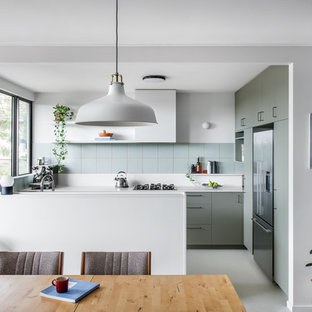 Photo of a mid-sized midcentury u-shaped eat-in kitchen in Brisbane with flat-panel cabinets, green cabinets, stainless steel appliances, a peninsula, grey floor, white benchtop and an undermount sink.