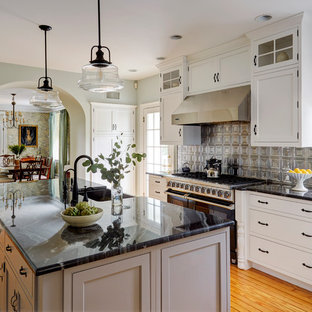 Large farmhouse kitchen designs - Example of a large farmhouse l-shaped medium tone wood floor and orange floor kitchen design in Philadelphia with a farmhouse sink, white cabinets, quartzite countertops, metallic backsplash, metal backsplash, stainless steel appliances, an island and shaker cabinets