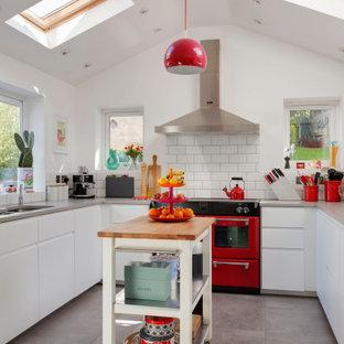 ケントの中サイズのエクレクティックスタイルのおしゃれなキッチン (アンダーカウンターシンク、フラットパネル扉のキャビネット、白いキャビネット、白いキッチンパネル、サブウェイタイルのキッチンパネル、シルバーの調理設備の、セラミックタイルの床、グレーの床、グレーのキッチンカウンター) の写真