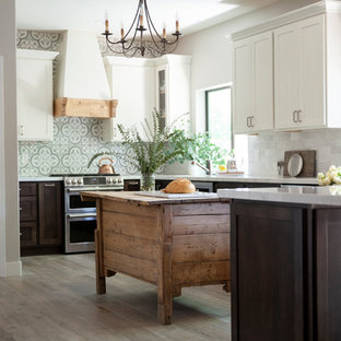 Country kitchen in Phoenix with a farmhouse sink, shaker cabinets, solid surface benchtops, multi-coloured splashback, cement tile splashback, stainless steel appliances, ceramic floors, with island and yellow benchtop.