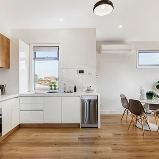 Design ideas for a contemporary l-shaped eat-in kitchen in Melbourne with a drop-in sink, flat-panel cabinets, white cabinets, white splashback, stainless steel appliances, medium hardwood floors, brown floor and white benchtop.
