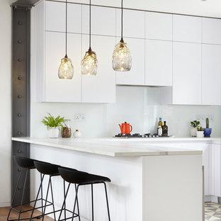 ロンドンの大きいコンテンポラリースタイルのおしゃれなキッチン (ドロップインシンク、フラットパネル扉のキャビネット、白いキャビネット、大理石カウンター、白いキッチンパネル、ガラス板のキッチンパネル、カラー調理設備、コンクリートの床) の写真