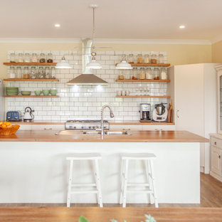 Photo of a country l-shaped kitchen in Other with a drop-in sink, flat-panel cabinets, white cabinets, wood benchtops, white splashback, subway tile splashback, stainless steel appliances, medium hardwood floors, with island, brown floor and brown benchtop.