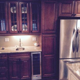 Mittelgroße Klassische Wohnküche in L-Form mit Unterbauwaschbecken, flächenbündigen Schrankfronten, schwarzen Schränken, Granit-Arbeitsplatte, Küchengeräten aus Edelstahl, braunem Holzboden, Kücheninsel und braunem Boden in Chicago