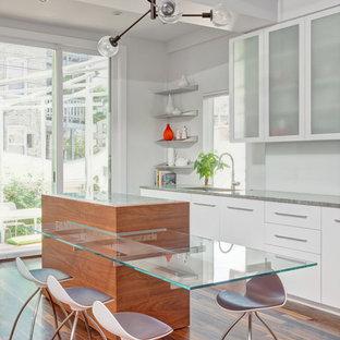 Immagine di una cucina abitabile minimal con ante lisce, ante bianche, pavimento in legno massello medio e isola