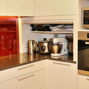 Large modern u-shaped kitchen pantry in Sydney with a built-in sink, flat-panel cabinets, beige cabinets, engineered stone countertops, red splashback, glass sheet splashback, stainless steel appliances, ceramic flooring and an island.
