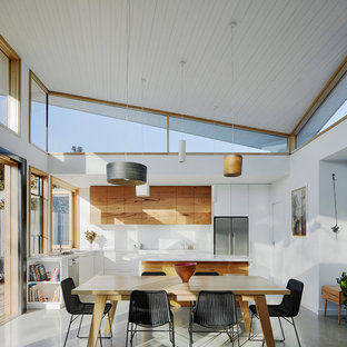This is an example of a mid-sized contemporary l-shaped eat-in kitchen in Melbourne with white splashback, multiple islands, grey floor, a drop-in sink, flat-panel cabinets, medium wood cabinets and stainless steel appliances.