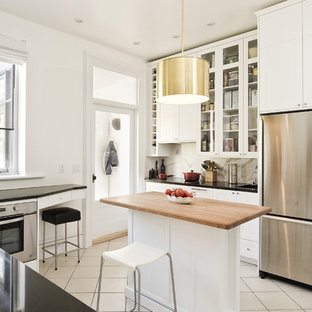 This is an example of a mid-sized contemporary separate kitchen in Montreal with glass-front cabinets, wood benchtops, white cabinets, stainless steel appliances, white splashback, stone slab splashback, ceramic floors, with island and beige floor.