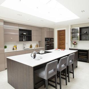 Inredning av ett modernt l-kök, med en undermonterad diskho, släta luckor, bruna skåp, en köksö och vitt golv