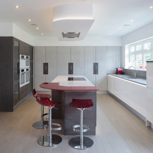 Inspiration for a contemporary kitchen in Other with a double-bowl sink, flat-panel cabinets, laminate benchtops, grey splashback, glass sheet splashback, with island, light hardwood floors and red benchtop.