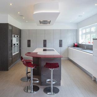 Идея дизайна: кухня в современном стиле с двойной раковиной, плоскими фасадами, столешницей из ламината, серым фартуком, фартуком из стекла, островом, светлым паркетным полом и красной столешницей
