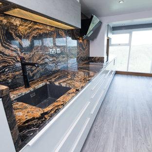 Idee per una cucina moderna con lavello da incasso, ante di vetro, ante in acciaio inossidabile, top in granito, paraspruzzi multicolore, paraspruzzi in lastra di pietra, elettrodomestici in acciaio inossidabile, pavimento in vinile, pavimento grigio e top multicolore