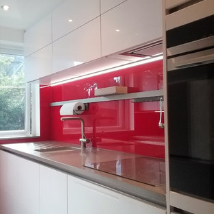 Small contemporary enclosed kitchen photos - Small trendy galley enclosed kitchen photo in West Midlands with an undermount sink, flat-panel cabinets, white cabinets, quartzite countertops, red backsplash, glass sheet backsplash and black appliances