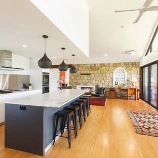 Mid-sized contemporary galley kitchen in Newcastle - Maitland with a drop-in sink, flat-panel cabinets, marble benchtops, medium hardwood floors, brown floor, white benchtop and with island.