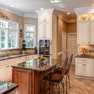 Imagen de cocina clásica con armarios con paneles con relieve, puertas de armario beige, salpicadero beige, electrodomésticos de acero inoxidable y salpicadero de piedra caliza