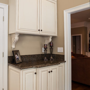 Large traditional eat-in kitchen appliance - Large elegant u-shaped porcelain floor eat-in kitchen photo in Charlotte with a single-bowl sink, raised-panel cabinets, white cabinets, granite countertops, stainless steel appliances and an island
