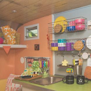 他の地域の小さいエクレクティックスタイルのおしゃれなキッチン (シングルシンク、フラットパネル扉のキャビネット、白いキャビネット、ラミネートカウンター、シルバーの調理設備の、クッションフロア、アイランドなし、グレーの床、緑のキッチンカウンター) の写真