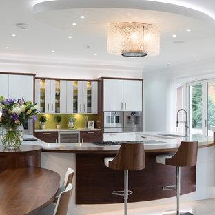 他の地域の広いコンテンポラリースタイルのおしゃれなキッチン (ドロップインシンク、フラットパネル扉のキャビネット、中間色木目調キャビネット、クオーツストーンカウンター、緑のキッチンパネル、ガラス板のキッチンパネル、パネルと同色の調理設備、白いキッチンカウンター、ベージュの床) の写真
