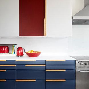 Idéer för ett modernt vit kök, med släta luckor, blå skåp, rostfria vitvaror, mellanmörkt trägolv och brunt golv