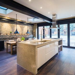 Modern inredning av ett kök och matrum, med släta luckor, vita skåp och mörkt trägolv