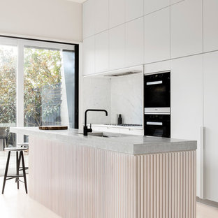 Mid-sized modern galley kitchen in Melbourne with an undermount sink, white cabinets, concrete benchtops, white splashback, stone slab splashback, black appliances, an island and flat-panel cabinets.