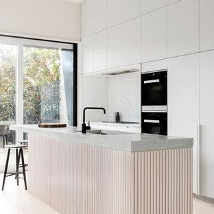 Modelo de cocina de galera, minimalista, de tamaño medio, con fregadero bajoencimera, puertas de armario blancas, encimera de cemento, salpicadero blanco, salpicadero de losas de piedra, electrodomésticos negros, una isla y armarios con paneles lisos