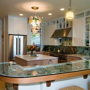 Modelo de cocina en U, tradicional, pequeña, cerrada, con fregadero bajoencimera, armarios estilo shaker, puertas de armario blancas, encimera de vidrio reciclado, salpicadero azul, salpicadero de azulejos de vidrio, electrodomésticos de acero inoxidable y una isla