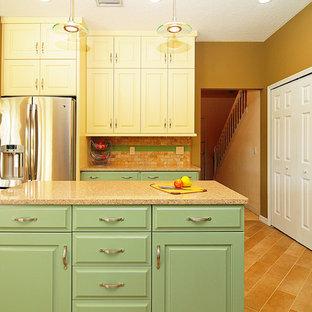 オーランドの中くらいのエクレクティックスタイルのおしゃれなキッチン (アンダーカウンターシンク、レイズドパネル扉のキャビネット、緑のキャビネット、クオーツストーンカウンター、ベージュキッチンパネル、石タイルのキッチンパネル、シルバーの調理設備、磁器タイルの床) の写真