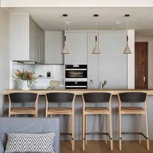 ロサンゼルスのコンテンポラリースタイルのおしゃれなキッチン (フラットパネル扉のキャビネット、グレーのキャビネット、木材カウンター、白いキッチンパネル、ガラス板のキッチンパネル、淡色無垢フローリング) の写真