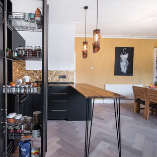 This is an example of a mid-sized contemporary u-shaped eat-in kitchen in London with flat-panel cabinets, black cabinets, quartzite benchtops, metallic splashback, metal splashback, black appliances, light hardwood floors, a peninsula and multi-coloured floor.