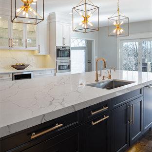 他の地域の広いトランジショナルスタイルのおしゃれなアイランドキッチン (アンダーカウンターシンク、フラットパネル扉のキャビネット、白いキャビネット、クオーツストーンカウンター、白いキッチンパネル、石スラブのキッチンパネル、シルバーの調理設備、濃色無垢フローリング、茶色い床、白いキッチンカウンター) の写真