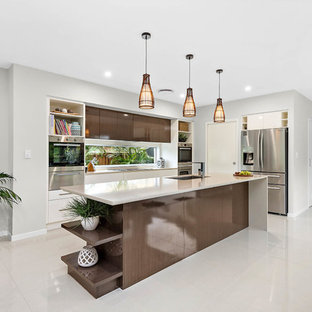 Photo of a contemporary l-shaped kitchen in Gold Coast - Tweed with an undermount sink, flat-panel cabinets, dark wood cabinets, window splashback, stainless steel appliances, with island and beige floor.